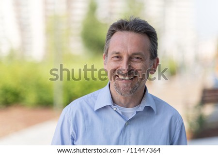 Mature man with blue shirt outdoors
