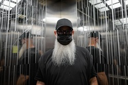 Mature man with gray beard wearing face mask for protection against corona virus Covid-19