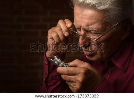 Mature man with pills in a shirt on a brick background - stock photo