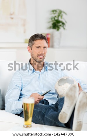 Mature man with soccer ball and remote control watching soccer match on television at home
