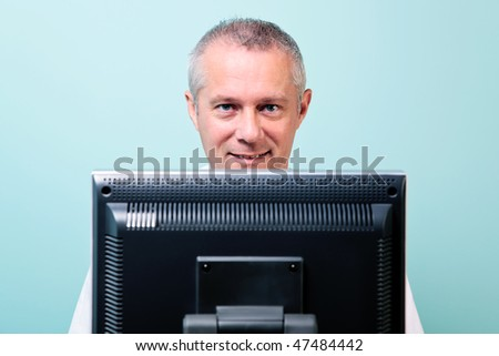 Mature man working at a computer looking over the screen