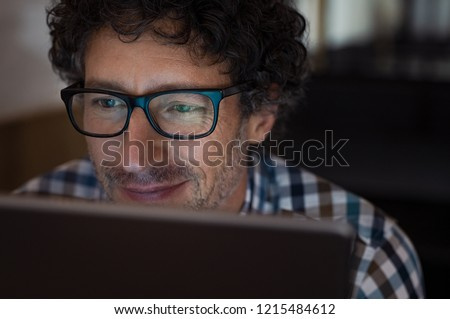 Mature man working on computer at night in dark office. Smiling business man wearing eyeglasses sitting at night working on laptop. Businessman wearing spectacles using digital tablet late at night.