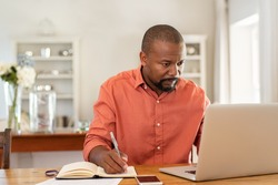 Mature man working on laptop while taking notes. Businessman working at home with computer while writing on agenda. African man managing home finance, reviewing bank account and using laptop.
