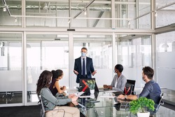 Mature manager in office discussing strategy with employees while wearing face mask during covid-19 pandemic. Group of multiethnic business people in meeting keeping social distancing in boardroom.