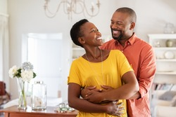 Mature married couple embracing in living room while looking at each other. Newly wed african couple in love hugging at home. Romantic husband with beautiful wife in love at home with copy space.