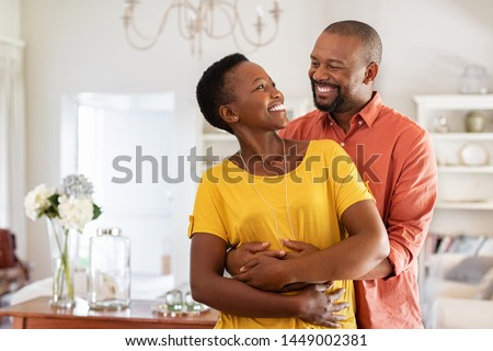 Mature married couple embracing in living room while looking at each other. Newly wed african couple in love hugging at home. Romantic husband with beautiful wife in love at home with copy space. Сток-фото ©