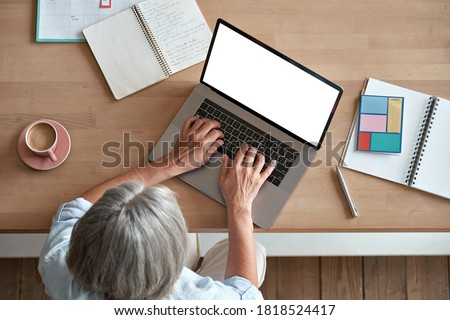 Mature middle aged business woman using laptop computer sitting at workplace desk. Senior older lady, 60s grey-haired businesswoman working at table typing on pc at home or from office, top view.