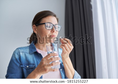 Mature middle-aged woman in casual clothes at home holding pill and glass of fresh water. Headaches, depression, medicine supplements vitamins, sedatives, menopause Foto stock ©