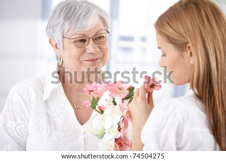 stock photo : Mature mother and young daughter smelling flowers, smiling.