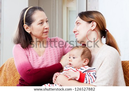 Mature mother gives solace to crying adult daughter with baby at home