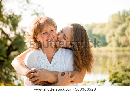 Mature mother hugging with her teen daughter outdoor in nature on sunny day #383388520