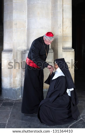 Mature nun kissing the ring of a cardinal in a medieval church - stock photo