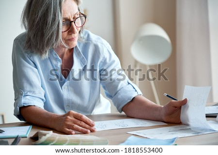 Mature old adult elegant woman fashion designer drawing creative sketches on table. Beautiful sophisticated middle aged grey-haired lady entrepreneur creating new fashion design cloth in atelier.
