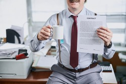 Mature old fashioned businessman holding lucrative contract and a cup of tea in hands with his office desk on background