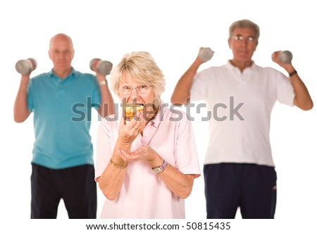 Mature older lady having a cheeky slice of cake with men working out at the gym