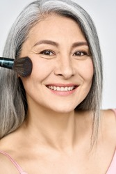 Mature older mid aged Asian woman of 50s with grey hair holding make up brush on radiant face with perfect skin. Advertising of radiant foundation skincare makeup for natural glow and healthy skin.