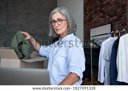 Mature older woman fashion designer, dropshipping online clothing store small business owner checking e commerce order on laptop preparing packing in postal mail delivery shipping box at workplace. Photo stock ©