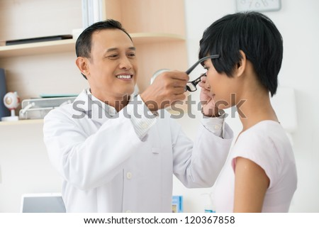 Mature optician giving new eyeglasses to female patient - stock photo