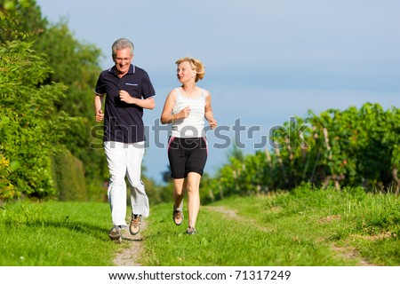 Mature or senior couple doing sport outdoors jogging down a path in summer