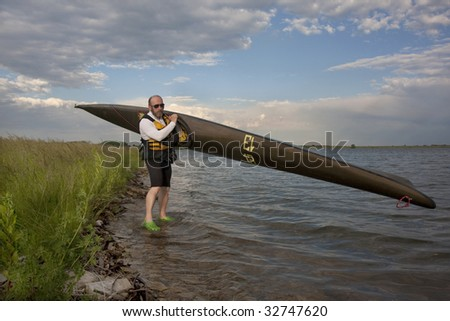 mature paddler is carrying  a long racing carbon fiber kayak to launch it on a lake with grassy and rocky shore in northern Colorado (thirteen - temporary race number placed on deck by myself)
