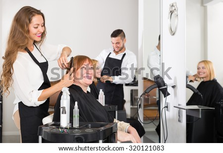 Mature person haircut at the hair salon with hairstylist and smiling
