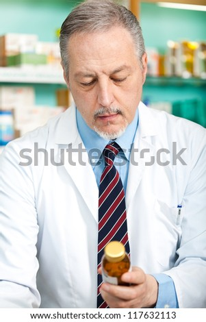 Mature pharmacist analyzing a product in his store