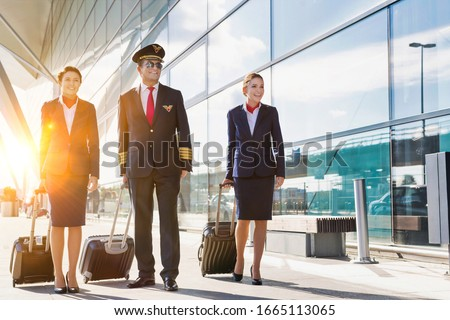 Mature pilot with young beautiful flight attendants walking in airport Photo stock ©