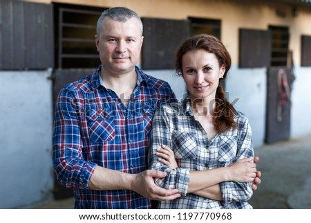 Mature positive family couple with belly-band standing  at stable outdoor