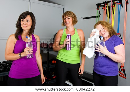 mature, pretty, women drinking water after a workout at a gym.
