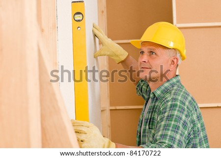 Mature professional handyman with spirit level working on home renovations