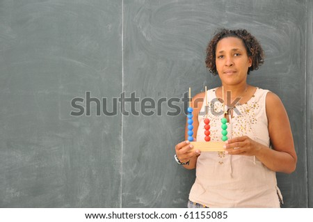 Mature Professional Woman Teacher in Classroom with Elementary School Abacus