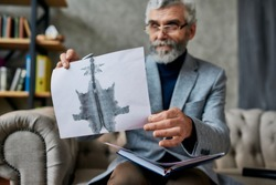 Mature psychologist holding picture with ink stain, Rorschach Inkblot during therapy session. Soldier suffering from depression, psychological trauma. PTSD concept. Focus on picture