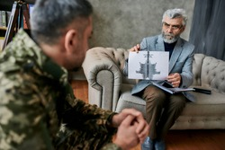 Mature psychologist holding picture with ink stain, Rorschach Inkblot in front of military man during therapy. Soldier suffering from depression, psychological trauma. PTSD concept. Focus on aged man