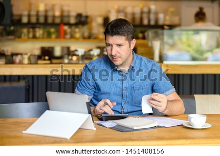 Mature restaurant owner calculating finance and bills of new business  – Entrepreneur online using tablet and calculator to work and calculate financial expenses of small coffee shop business start-up