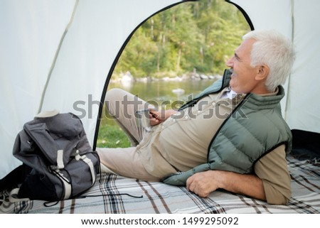 Mature restful man with hot tea lying in tent while looking at river and scenery during trip on summer weekend #1499295092