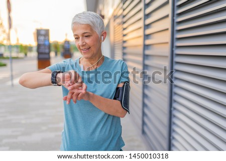 Mature Runner Checking Smart Watch. Checking Fitness Statistics On Smart Watch. Athletic mature woman monitoring her running performance on smartwatch