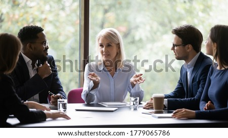 Mature 60s leader ceo company boss give helpful information to young diverse professionals teach them provide knowledge share ideas and strategic plans motivating to fruitful work, mentoring concept Сток-фото ©