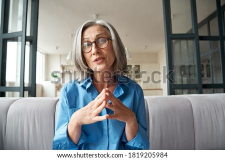 Mature 60s old woman online teacher, remote tutor, distance coach therapist businesswoman talking to web cam virtual counseling conference video calling at home office. Headshot portrait. Webcam view.