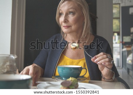 Mature 50s years old woman dressed on yellow t-shirt and blazer drinking coffee on cafe indoors with eclair.