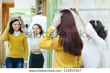 Mature saleswoman helps bride chooses bridal accessories at shop of wedding fashion. Focus on reflection