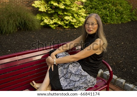 Mature, senior Asian woman seated on a red metal bench has feet up to take a break