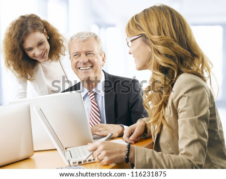 Mature (senior) business man discussing project with his colleagues. They working on laptop.