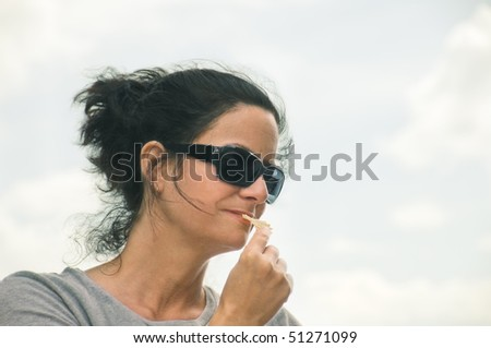 stock photo : mature sexy woman with sunglasses tasting chips - space to ...