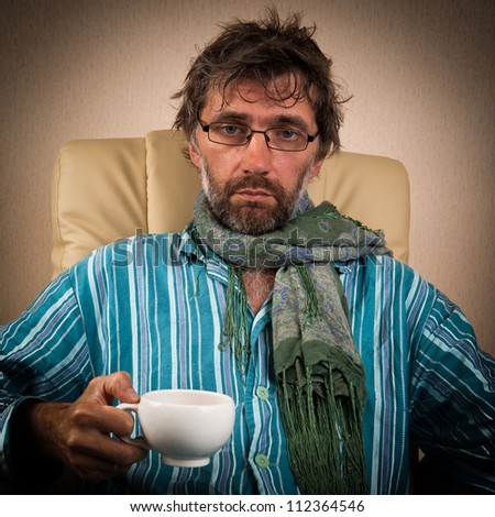 mature sick man sitting in chair with cup