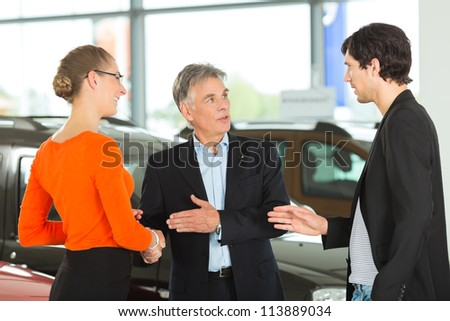 Mature single man with autos, handshaking in light car dealership with a young couple, he obviously is buying a car or is a car dealer