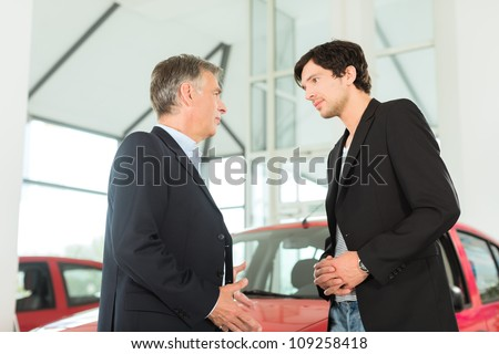 Mature single man with red auto in light car dealership with a male customer, a young man, he is obviously buying a car or is a car dealer