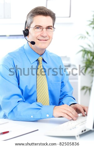 Mature smiling business man in modern office.