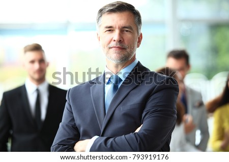 Mature smiling business manager crossing his arms in front of his business team