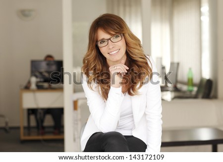 Mature smiling businesswoman sitting in her office