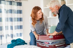 Mature smiling couple trying to close overstuffed suitcase with too much clothes for vacation. Senior man and mid woman having fun while packing suitcase full with clothes for holiday, copy space.